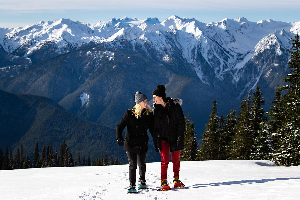 A smiling and happy couple snow shoeing during their adventure engagement photo session at Hurricane Ridge in Olympic National Park