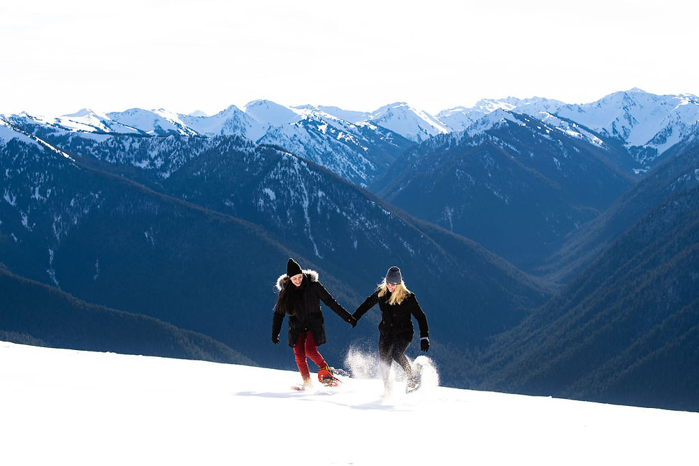 A couple running in the snow surrounded by mountain peaks for their adventure engagement photo session at Olympic National Park
