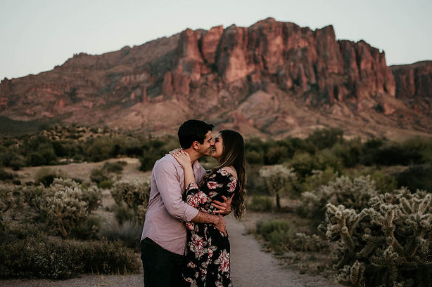 A gorgeous couple shares laughter and an intimate moment during their adventure engagement photography session in the Arizona desert