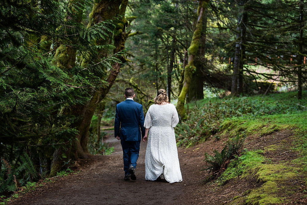 A couple walking through the rainforest on their Olympic National Park elopement in Washington