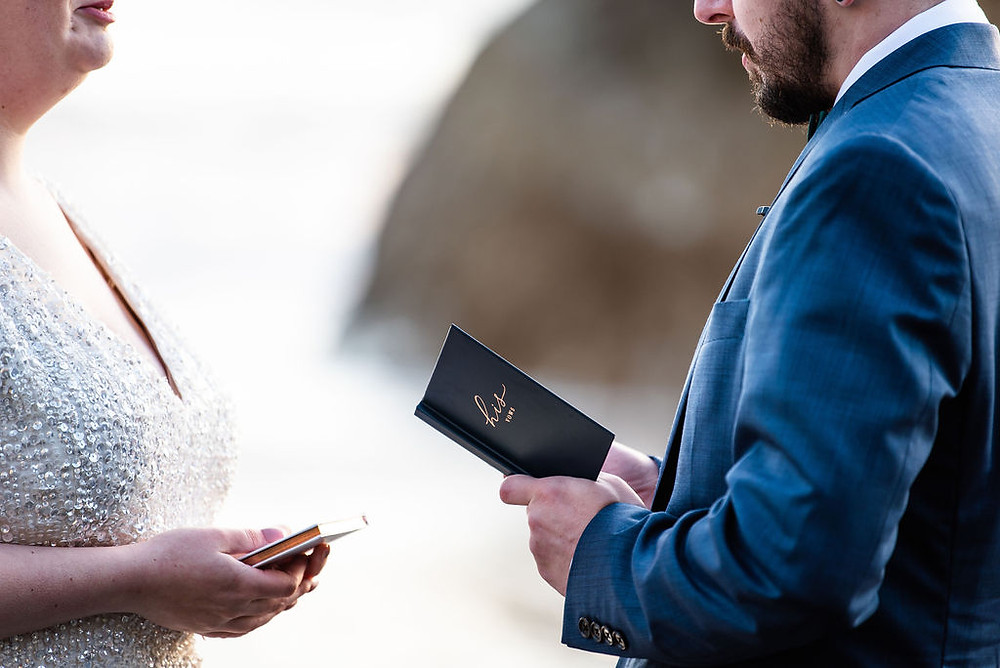 A closeup of a groom saying his vows on the beach