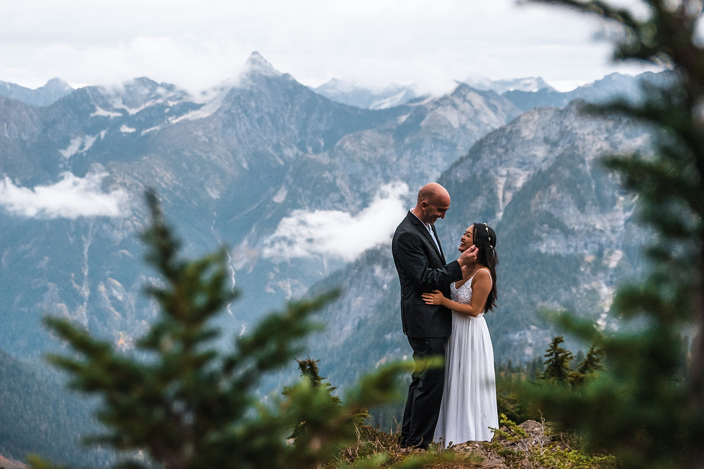 A couple laughs together on their adventure wedding day near North Cascades National Park and Mount Baker