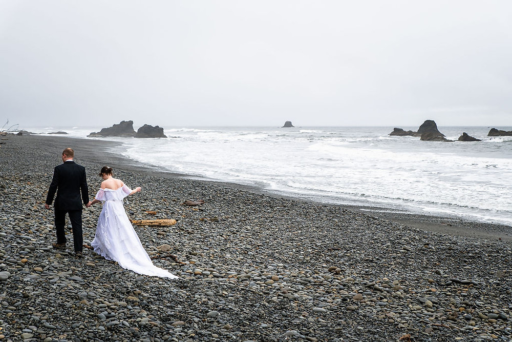 A couple walks along the beach on their elopement day during their Olympic National Park adventure elopement