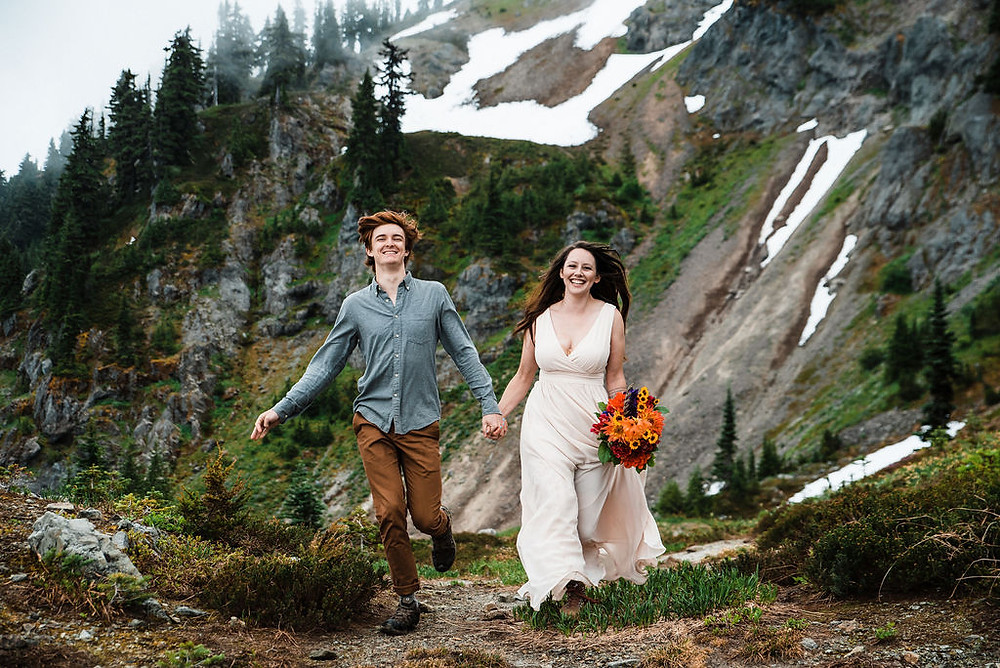 A couple eloping and running in the remote alpine outside of Mount Rainier National Park