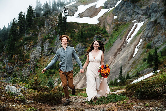 A couple running in the alpine wilderness outside of Mount Rainier National Park on their adventure elopement day