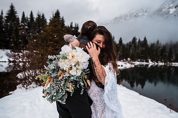 A couple hugging near a lake during their snowy, winter elopement