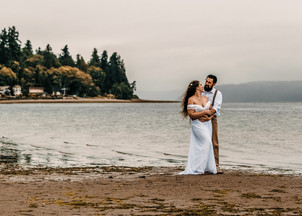 A bridal couple gazes into each other's eyes on their adventure elopement day on a private Washington beach