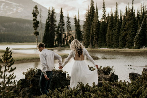 A groom leads his bride as they hike through the forest on their wedding day.