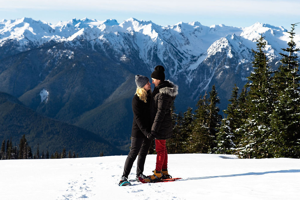 A couple hugging in front of mountains while surrounded by snow for their engagement pictures