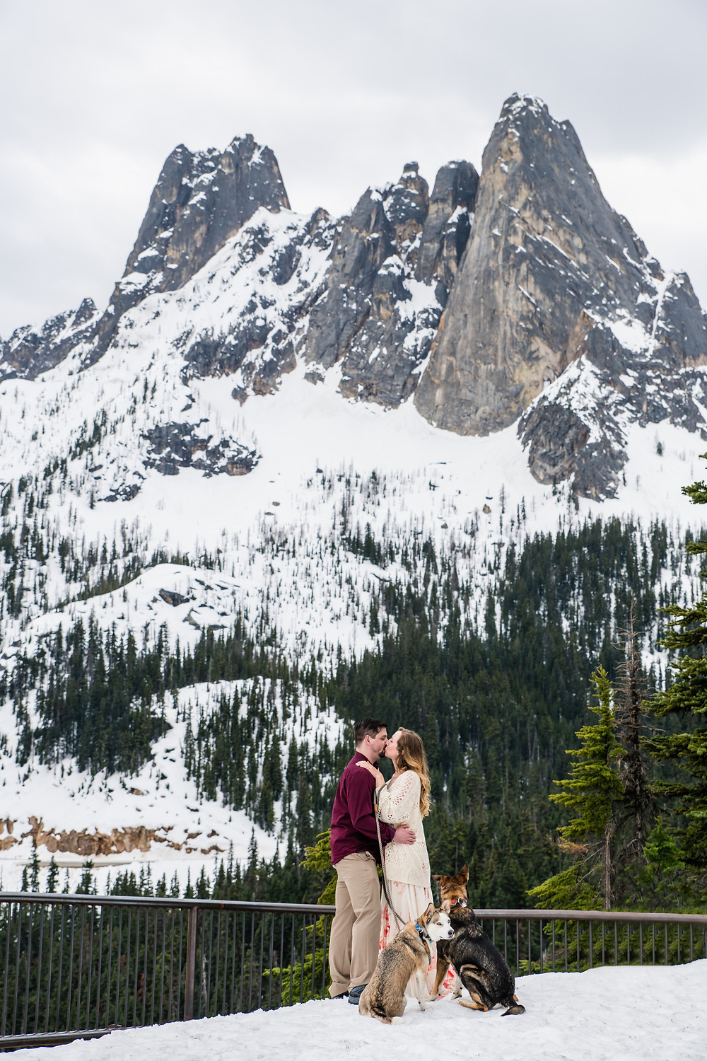 A couple kisses in the snow during their North Cascades elopement with their dogs
