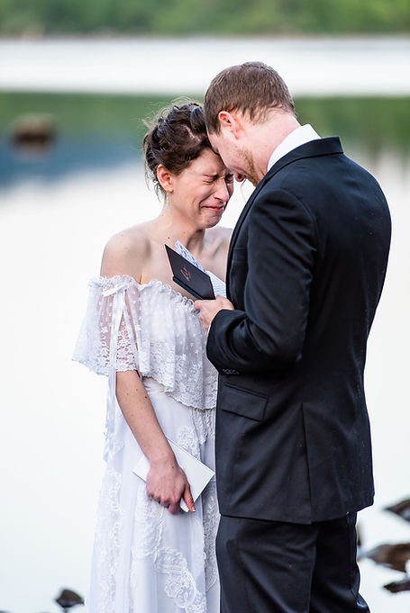 A bride crying during the vow reading at their elopement ceremony in Washington by a lake