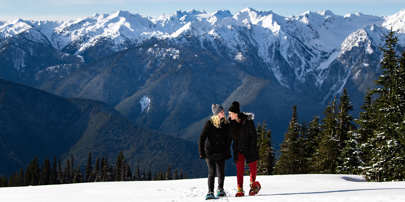 A couple snowshoeing during their adventure engagement photos at Hurricane Ridge in Olympic National Park