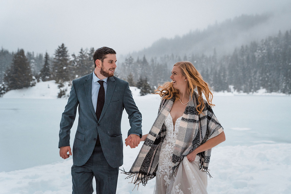 A happy couple running through the snow on their elopement day at Gold Creek Pond