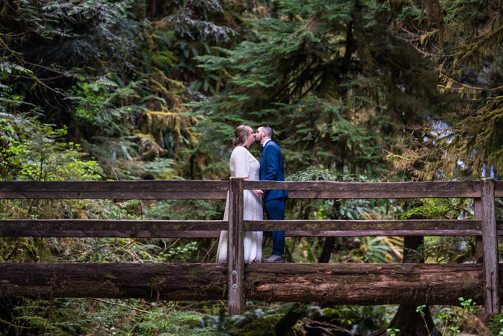 A couple kissing on a bridge on their adventure elopement day in the rainforest in Olympic National Park
