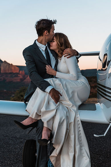 A couple cuddling on the wing of a plane at sunset during their stunning Sedona elopement