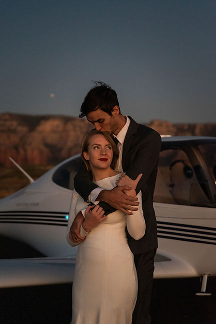 A couple cuddling at dusk in front of an airplane during their Sedona elopement