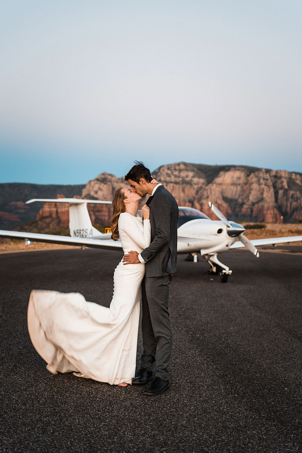 A couple on their elopement day in front of a plane in Sedona