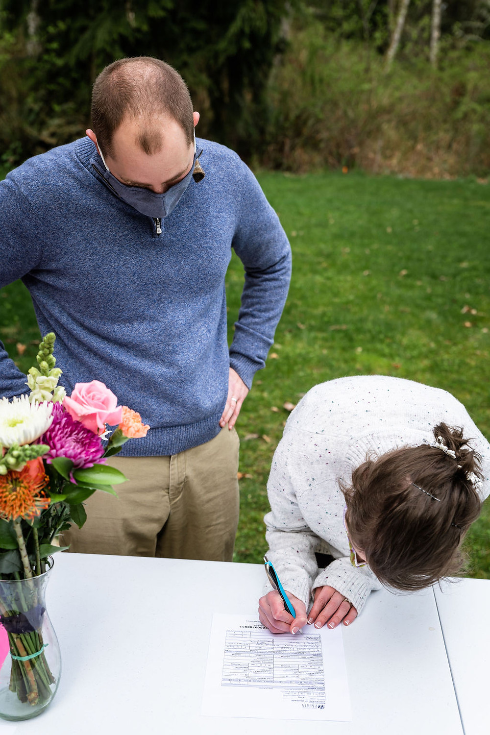 A couple signing their marriage license on their Washington elopement day