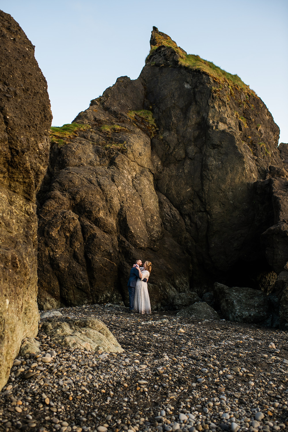 A couple cuddling and hugging at sunset in front of a sea stack at Ruby beach during their Olympic National Park elopement