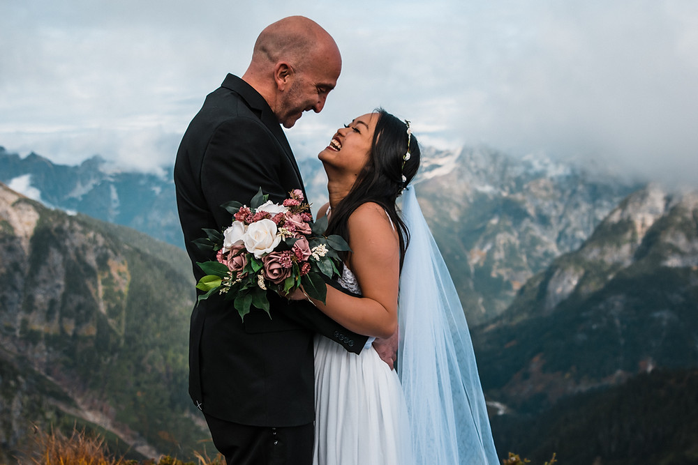 A bride laughs up towards her smiling groom with a stunning mountain range behind them during their elopement in the North Cascades