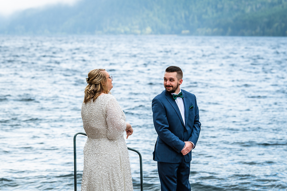 A couple sharing a few moments on their elopement day when the groom saw his bride for the first time on their elopement day on Lake Crescent
