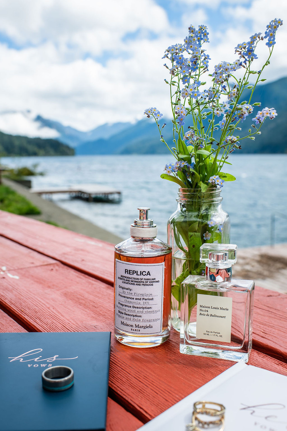 A couple's elopement details sitting on a bench in front of Lake Crescent in Olympic National Park
