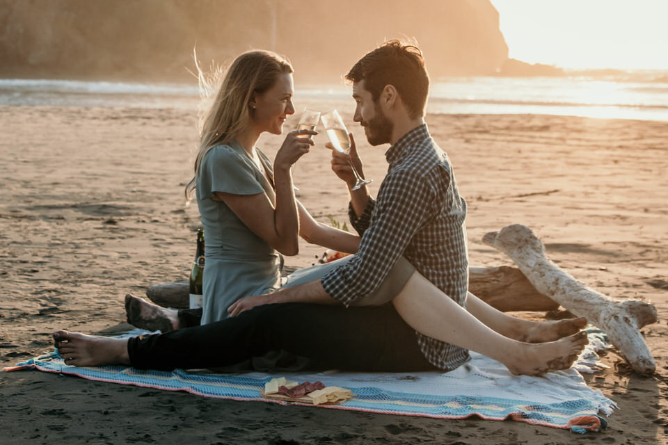 A couple toasting champagne during their engagement photos on Ruby Beach in Washington