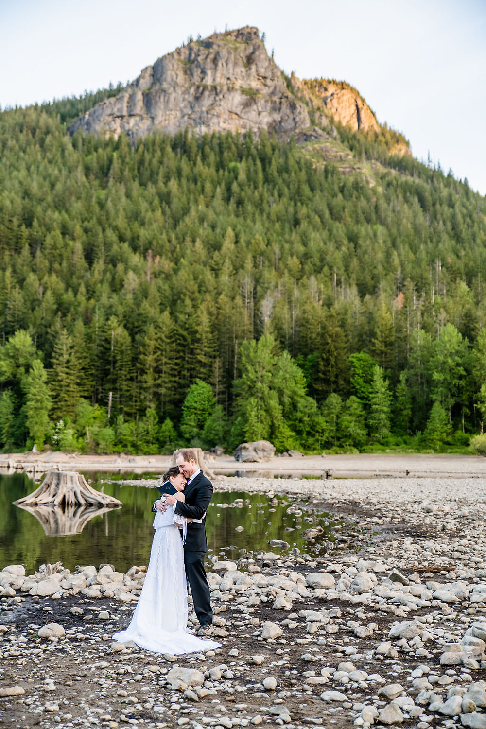 A bride and groom taking a moment to cuddle during their vows at sunrise in Washington by a lake