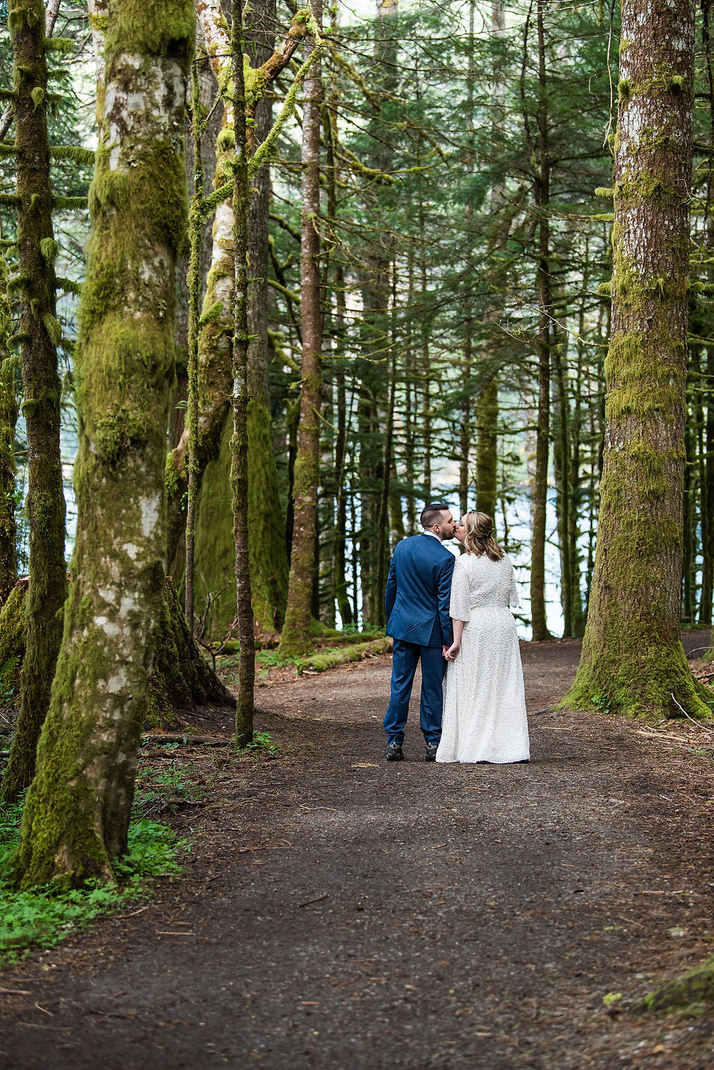 A couple walks though the rainforest on their adventure wedding day in Olympic National Park