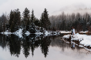 A bride and groom dance in the snow and are reflected onto a gorgeous alpine lake during their adventurous wedding day
