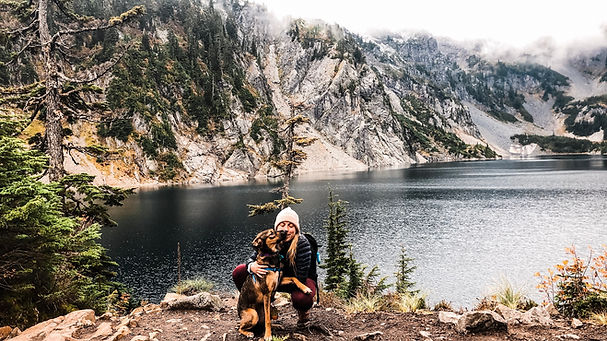 An adventure elopement photographer and guide plays with her dog in front of a snowy alpine lake up in the Snoqualmie National Forest in Washington