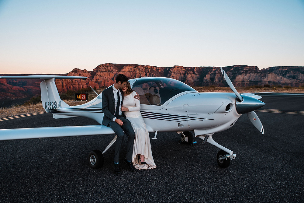 A wedding couple cuddling on the wing of an airplane during a Sedona sunset