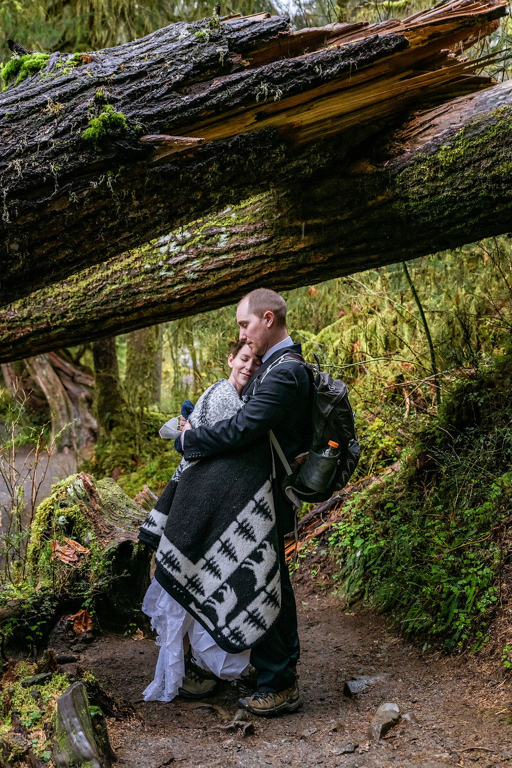 A couple hugging under the trees during their Hoh Rainforest elopement in Olympic National Park
