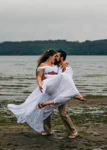 A bride is carried by her groom on the beach on their adventure elopement day