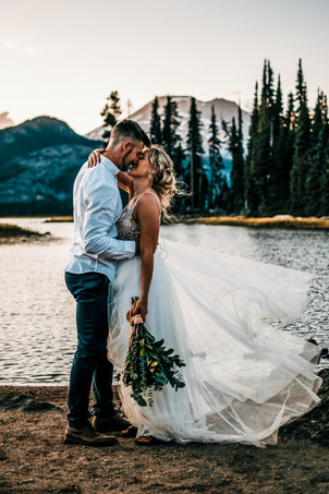 A bride's gorgeous dress is displayed in the wind in front of an alpine lake and mountains on their adventurous wedding day