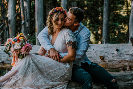 A groom kisses his bride on the cheek on their elopement day in the mountains
