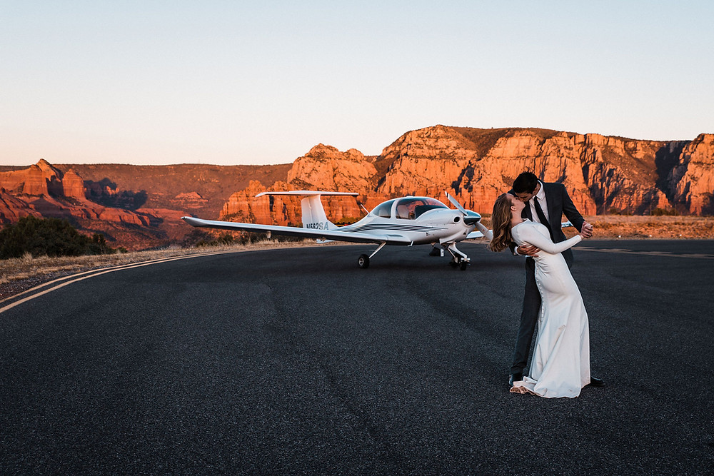A couple kissing in front of the sunset in Sedona during their wedding