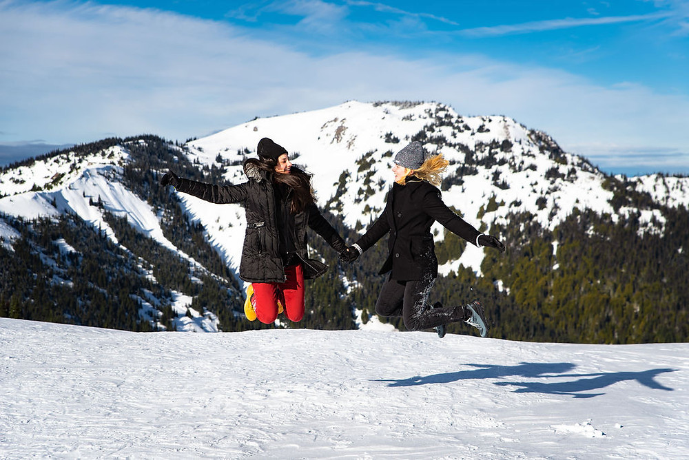 A couple jumping in the air in the snow for their adventure engagement photos at Hurricane Ridge