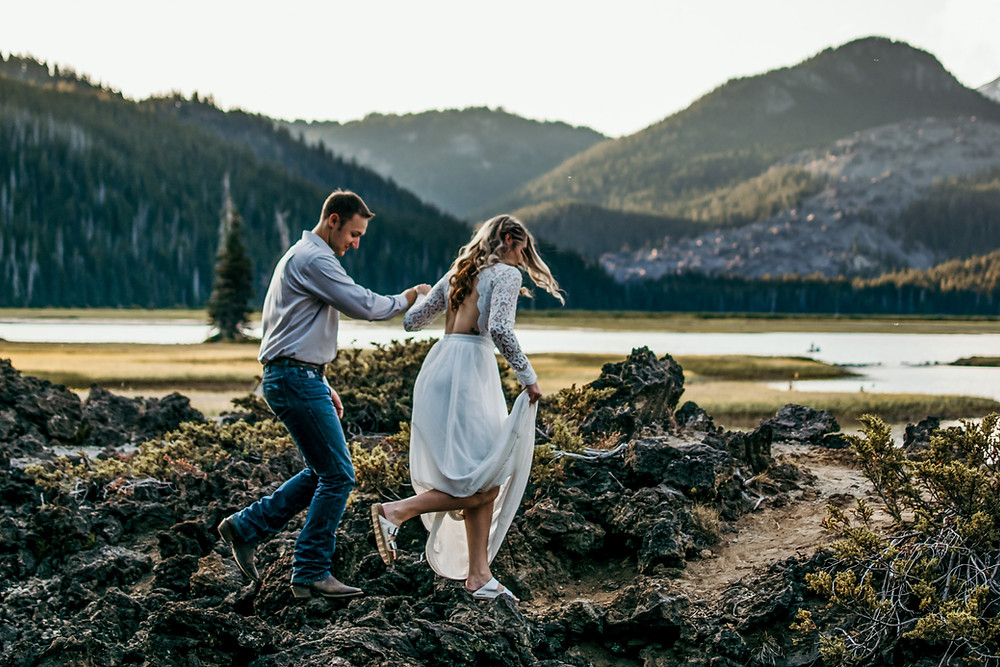 A bride and groom hike over a rocky trail in front of a beautiful alpine lake and in front of stunning tree covered mountains in Washington