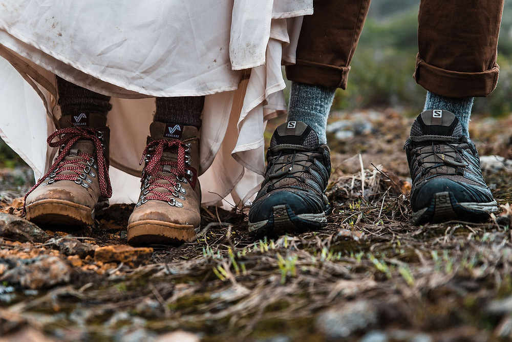 Hiking boots of an eloping couple hiking on their wedding day