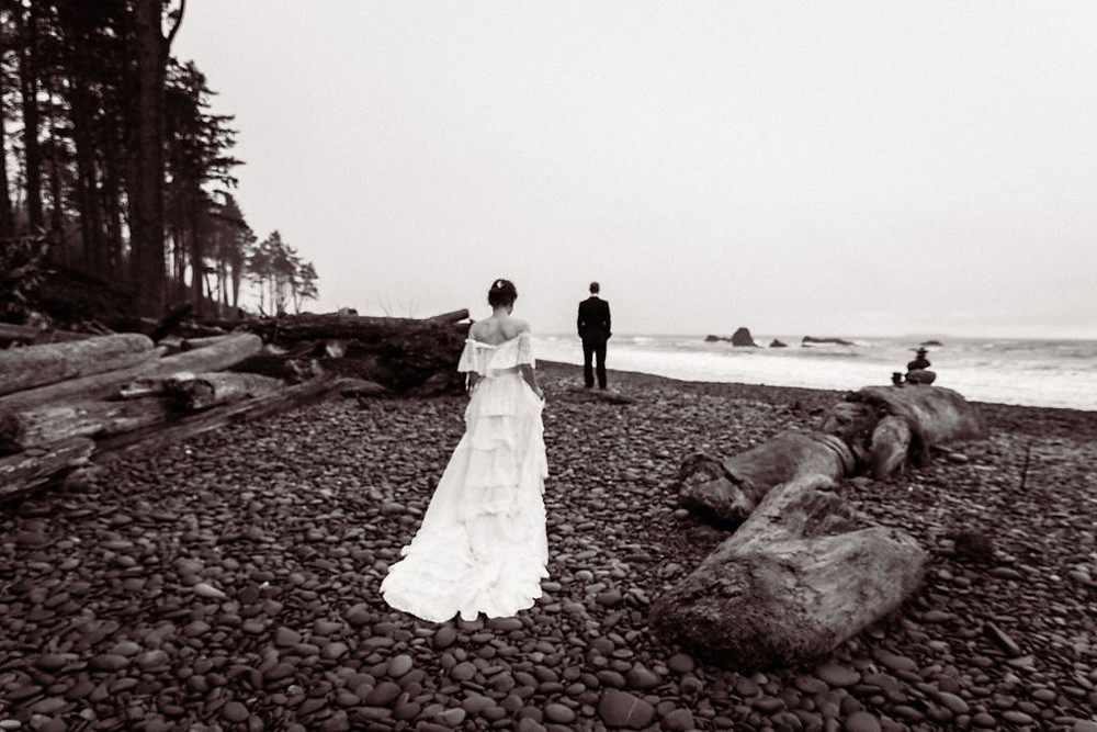 A bride walks towards her groom on Ruby Beach for their first look during their Olympic National Park elopement
