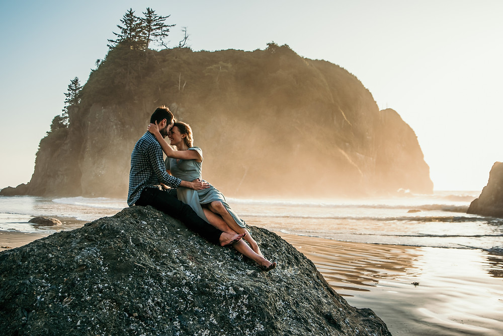 A couple gazes lovingly into eachother's eyes as they sit on a rock on the rugged coastal beach of Washington during their adventure engagement session