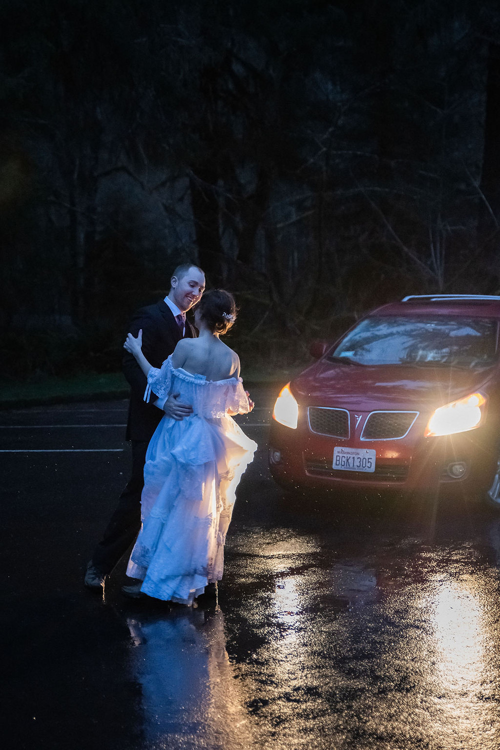 A couple dances in the headlights of their car on their Olympic National Park elopement day in the Hoh Rainforest