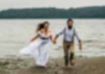 A laughing, happy, bridal couple runs on the beach together holding hands on their elopement day in Washington