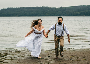 A couple on their adventure elopement day runs on the beach together, smiling and holding hands on a Washington beach