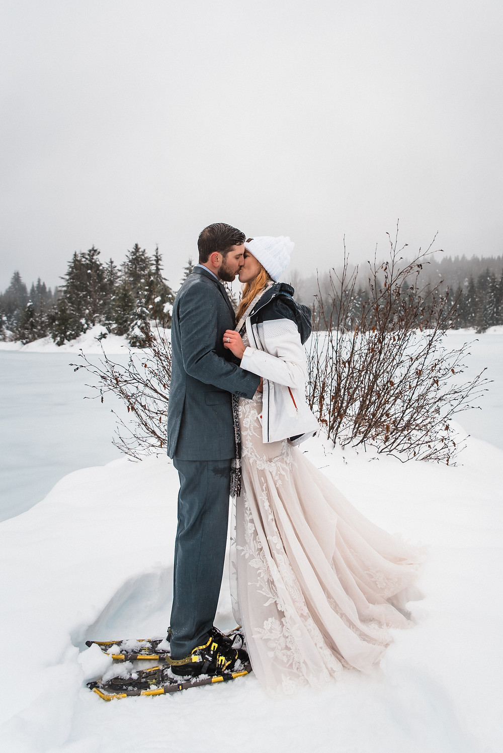 A couple kissing after getting married during their snowy elopement in Washington
