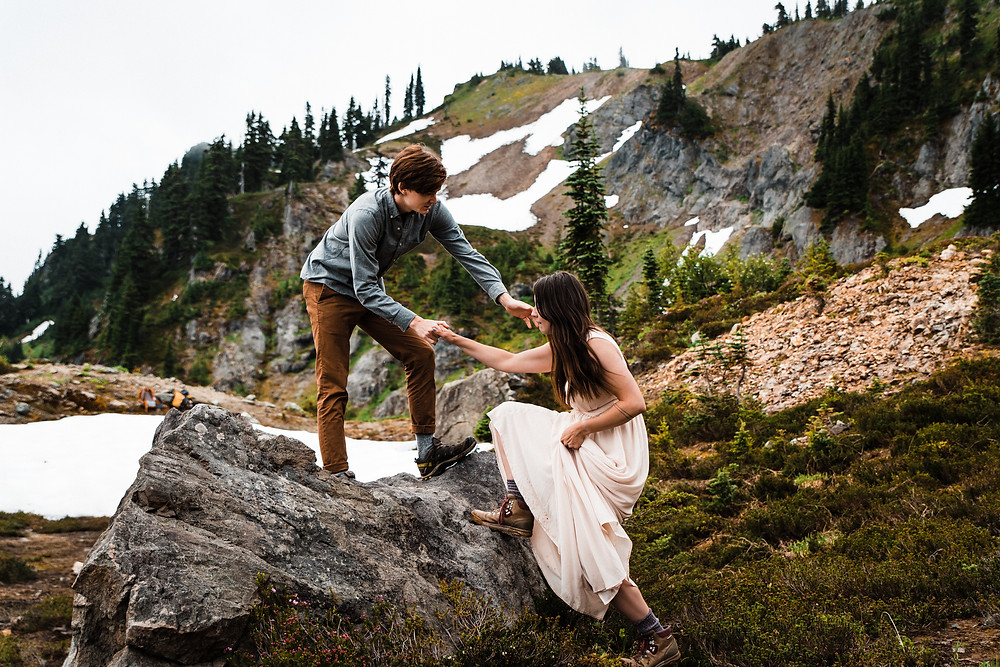 Bride and Groom climbing a rock during their Mount Rainier Elopement