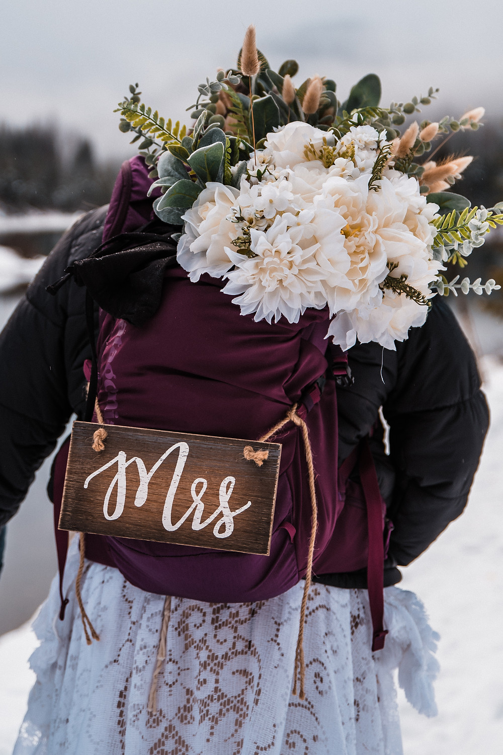 A bouquet is placed in a bride's hiking day pack as she prepares to begin hiking with her future husband on their adventurous wedding day