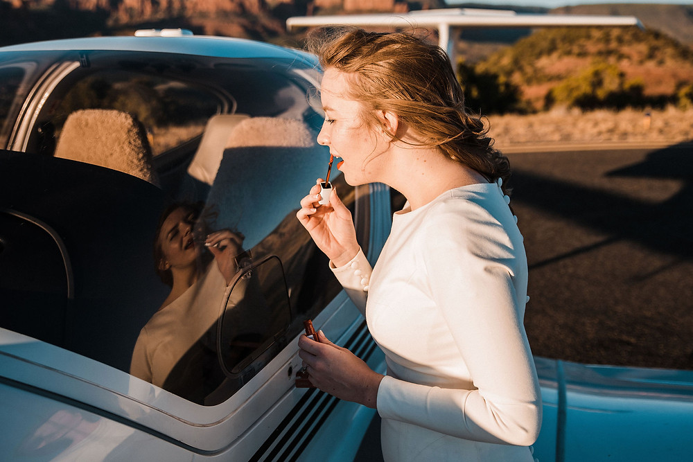 A bride putting on her lipstick in the reflection of a plane window