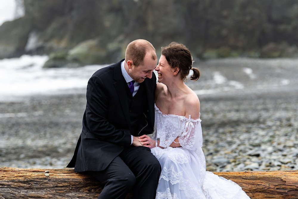A couple laughing with one another on the beach during their Olympic National Park elopement